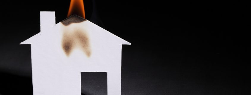 An orange flame burning the roof of a little paper house